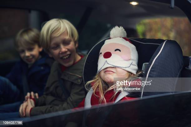 children in the car going christmas shopping - pere noel voiture photos et images de collection