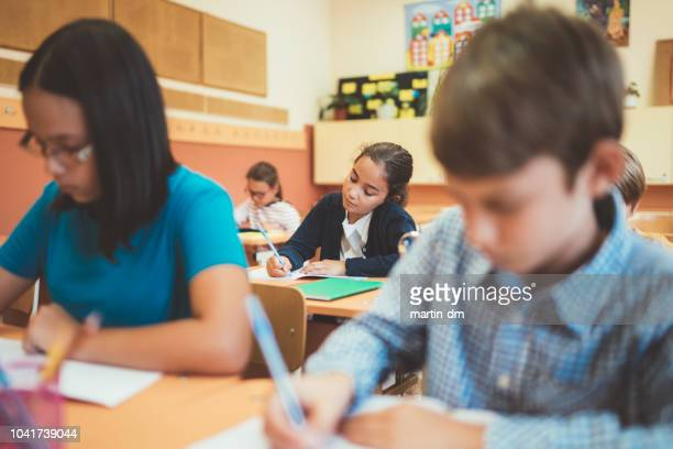 children in the classrom writing on exam - bulgaria stock pictures, royalty-free photos & images