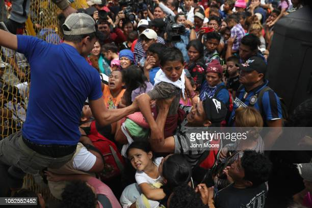 Children in the migrant caravan are lifted over a gate at the GuatemalaMexico border on October 19 2018 in Ciudad Tecun Uman Guatemala The caravan of...
