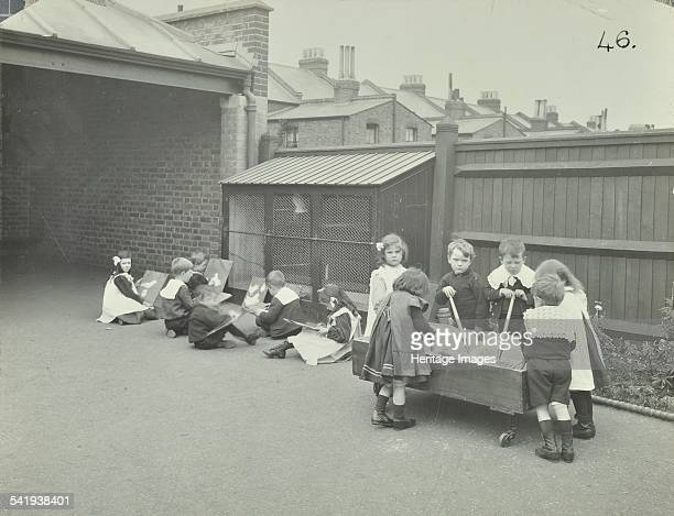 Children in the playground Southfields Infants' School Wandsworth London 1906 Some of the children are sitting on the ground drawing from nature...
