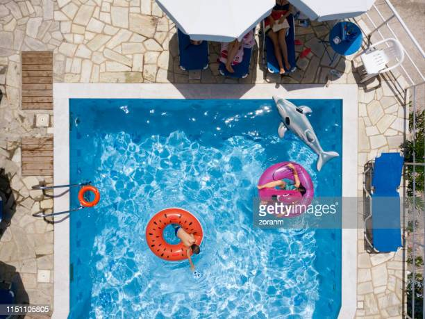 children in the pool on inflatables, adults resting at the poolside - swimming float stock pictures, royalty-free photos & images