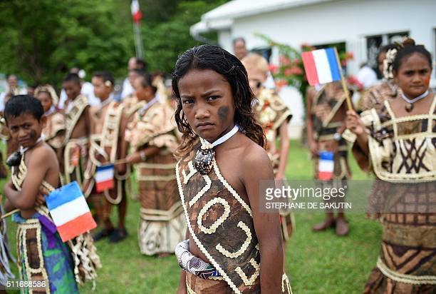 Children in traditional costumes hold French flags as they wait for French President Francois Hollande arrival Futuna island on February 22 during...