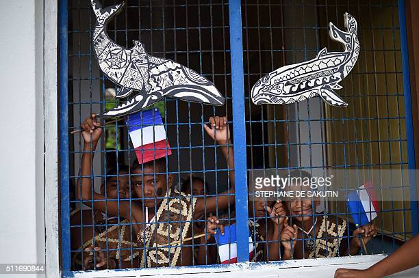 Children in traditional costumes hold French flags behind afence as they wait for French President Francois Hollande arrival in Futuna island on...