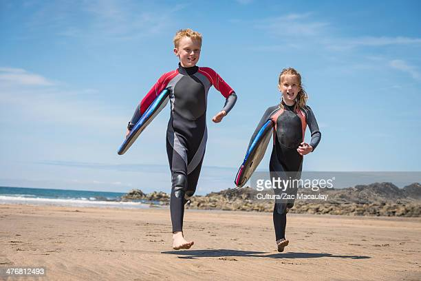 Children in wetsuits carrying surfboards