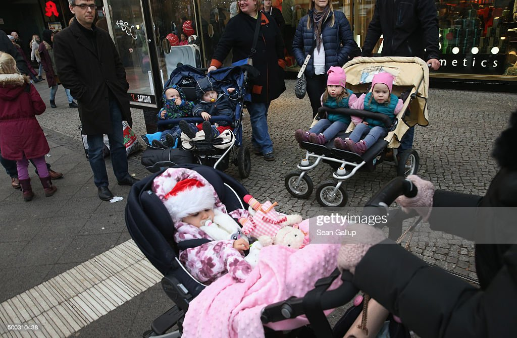 Children, including one and two-year-old boys (in dark blue) and three-year-old twin girls (with pink hats), and whose parents were present and agreed to the children being photographed, wait with their parents at a bus stop on December 6, 2015 in Berlin, Germany. For decades Germany has experienced a low birth rate, though recent statistics indicate a slight upward trend.