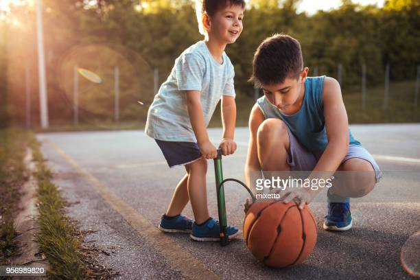 children inflating the ball - air pump stock photos and pictures