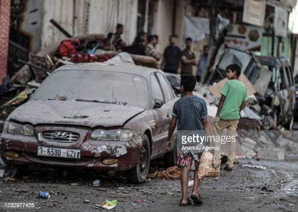 Children inspect a damaged vehicle after Israeli army carried out airstrike over a building in Sheikh Ridvan neighbourhood in Gaza City, Gaza on May...