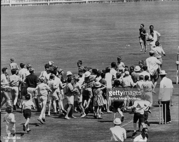 Children invade the ground to Congratulate Walters after he reaches his double Century. .