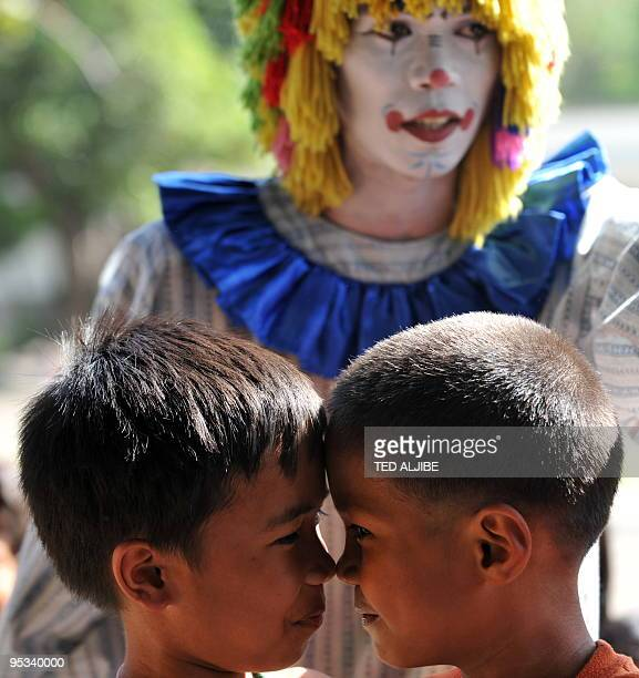 Children join a game as a clown watches during a program organized by the military to entertain evacuees from villages affected by rumbling Mayon...