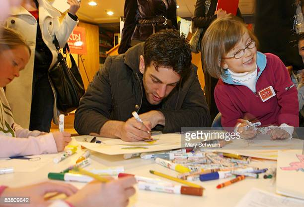 Children join BJ Novak writer and coexecutive producer of the NBC comedy series The Office as they work on drawings during the launch party of Kidz B...