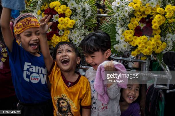 Children jubilate as they are doused with holy water as they take part in a parade of Black Nazarene replicas ahead of the Feast of the Black...