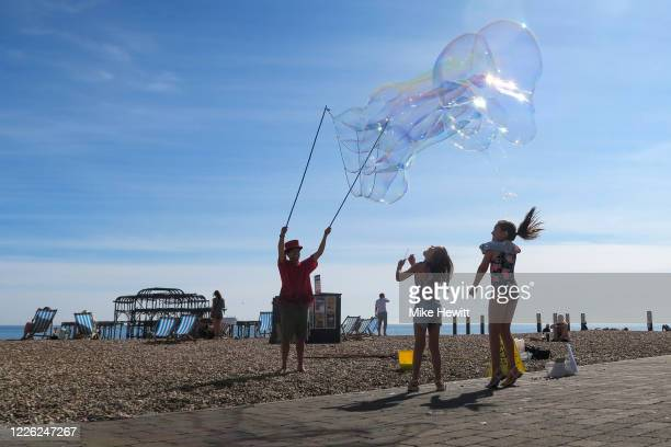 Children jump after giant bubbles on Brighton beach on May 21 2020 in Brighton England The British government has started easing the lockdown it...