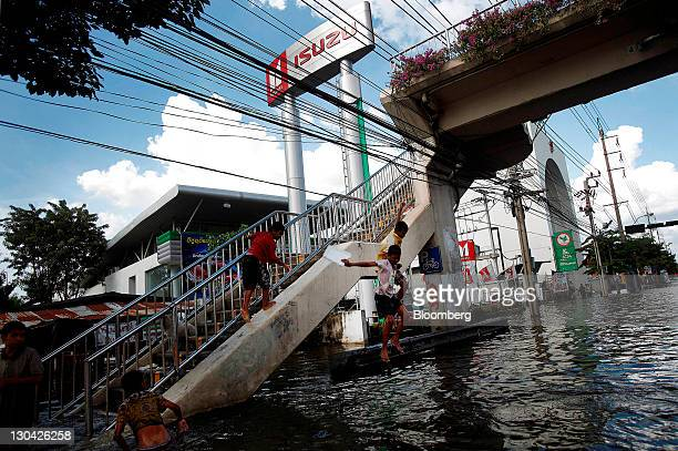 Children jump into flood waters in front of an Isuzu Motors Ltd car dealership in Bangkok Thailand on Wednesday Oct 26 2011 Thai Prime Minister...