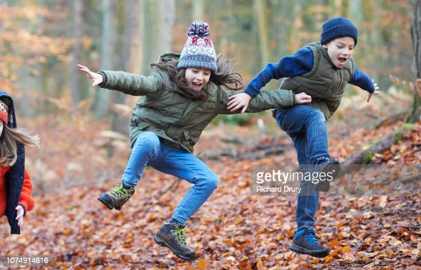 children jumping for joy in autumnal woodland - 10歳から11歳 ストックフォトと画像