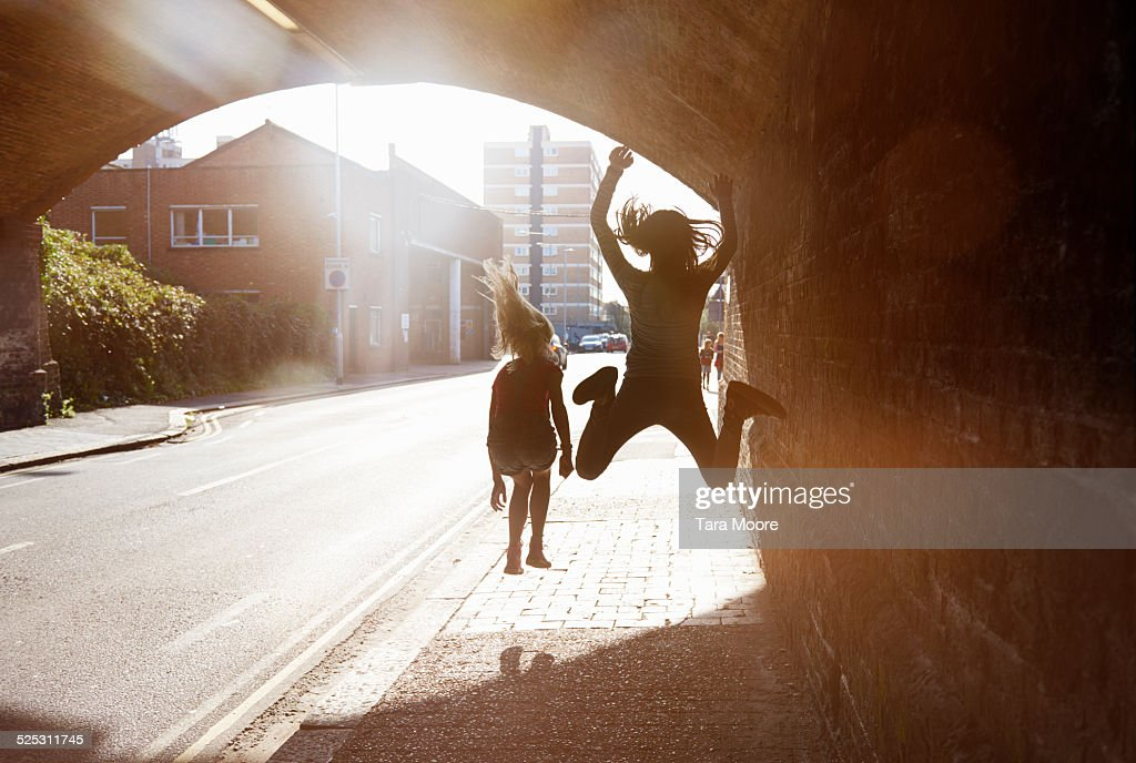 2 children jumping for joy in tunnel : Stock Photo