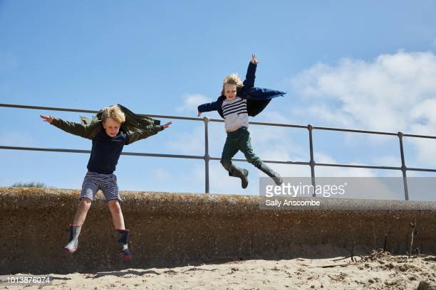 Children jumping from a wall