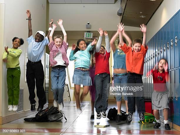 Children (8-10) jumping in school hallway (blurred motion)