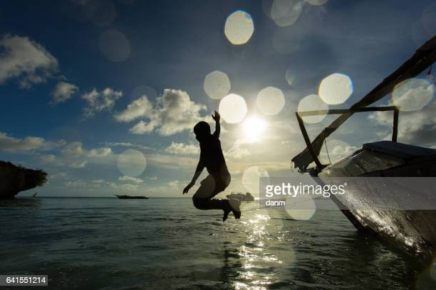 Children jumping in water from the boat in Zanzibar, Tanzania