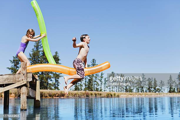 Children jumping into lake from jetty