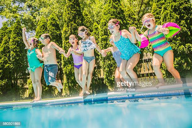 Children jumping into swimming pool