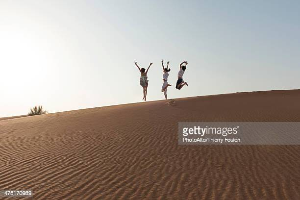Children jumping on top of dune with arms raised in air