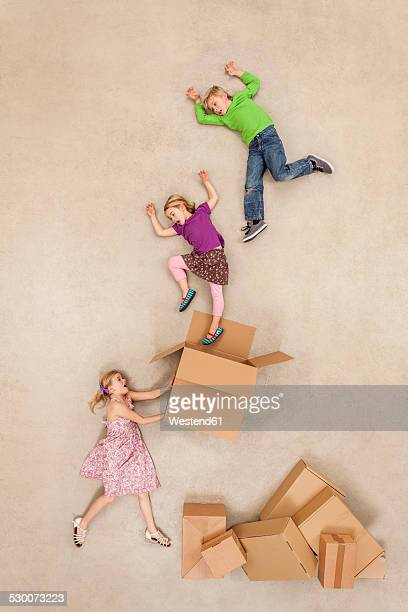 Children jumping out of cardboard boxes