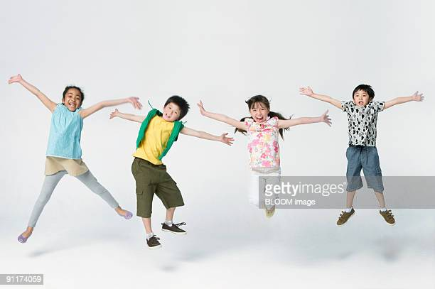 Children jumping, outstretching arms, studio shot