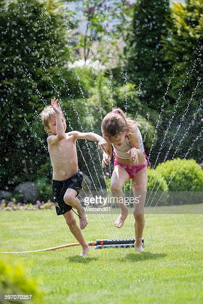 children jumping over sprinkler in garden - sprinkler system stock pictures, royalty-free photos & images