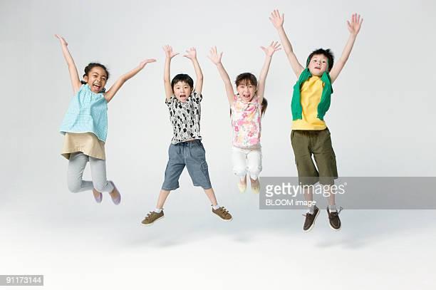 children jumping, raising hands, studio shot - 腕を上げる ストックフォトと画像