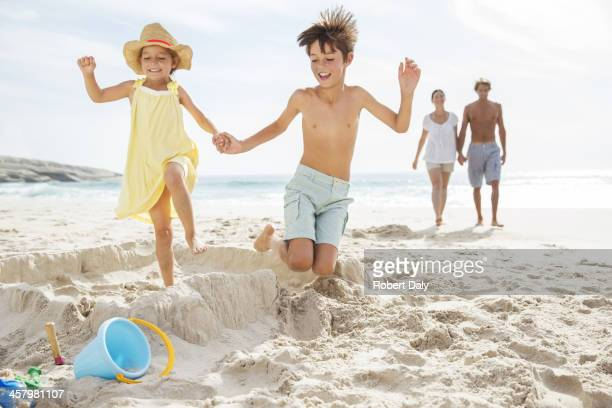 Children kicking down sandcastle on beach