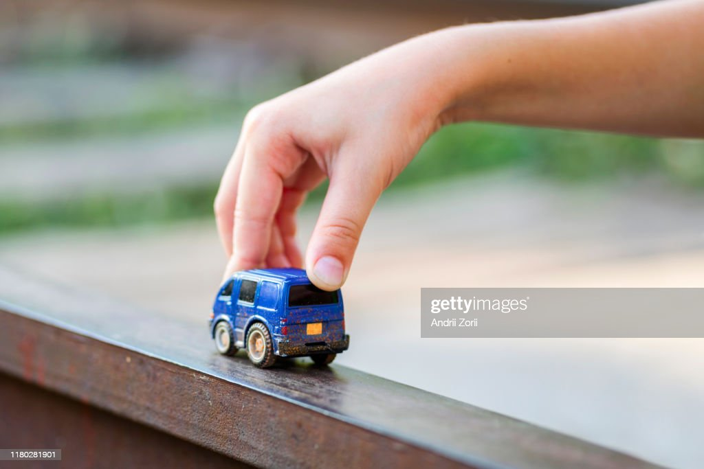 Children kid playing blue color car toy. Child hand playing with car : Stock Photo