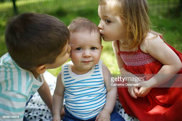 2 children kissing their baby brother
