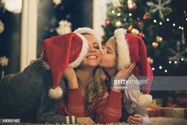 Children kissing their mother at Christmas