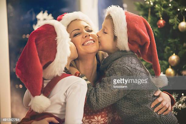 children kissing their mother on christmas - little girls giving head stock photos and pictures