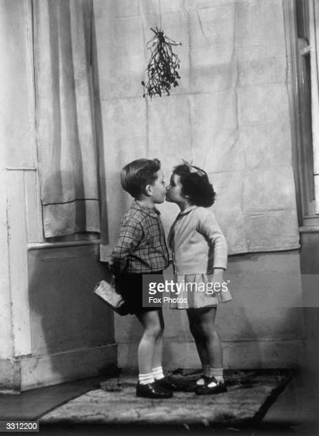 Children kissing under the mistletoe