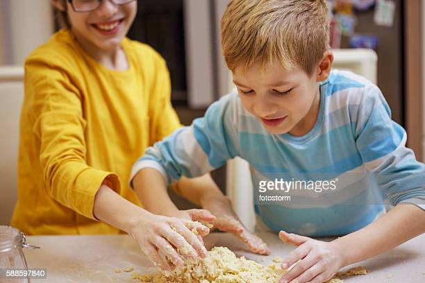 Children kneading dough together.
