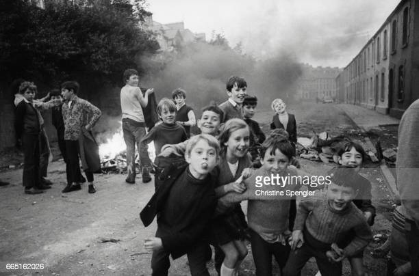 Children laughing and playing in a Londonderry street near a bonfire