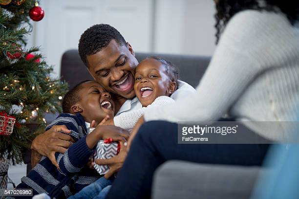 Children Laughing on Christmas Morning with Their Dad
