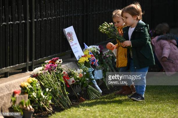Children lay flowers among the tributes left near Windsor Castle in Windsor, west of London, on April 14 following the April 9 death of Britain's...