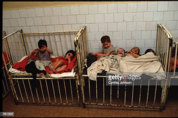 Children lay in a bed in an orphanage May 14 1990 in Vulturesti Romania The orphanage is for children who have birth defects such as retardedness and...