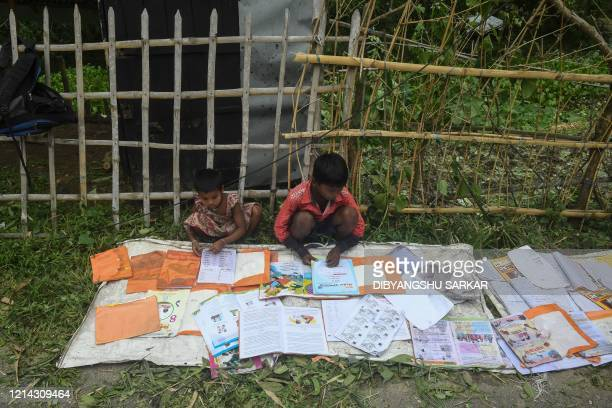 Children lay out their wet textbooks to dry following the landfall of cyclone Amphan in Khejuri area of Midnapore West Bengal on May 21 2020 At least...