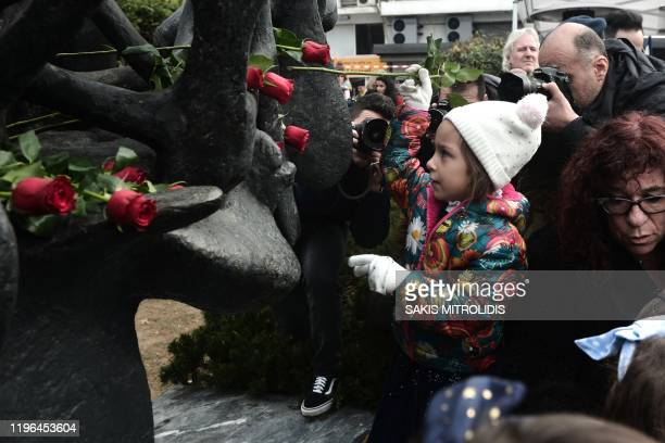 Children lay roses at the Holocaust Memorial monument downtown Thessaloniki on January 26 during the International Holocaust Remembrance Day which...