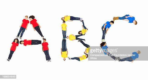 children laying in 'abc' formation - single word stock pictures, royalty-free photos & images