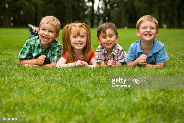 Children laying in grass in park