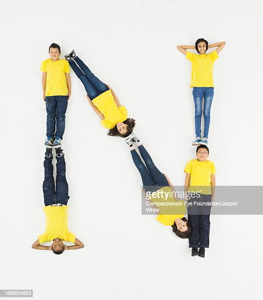 children laying in letter 'n' formation - letter n stock pictures, royalty-free photos & images