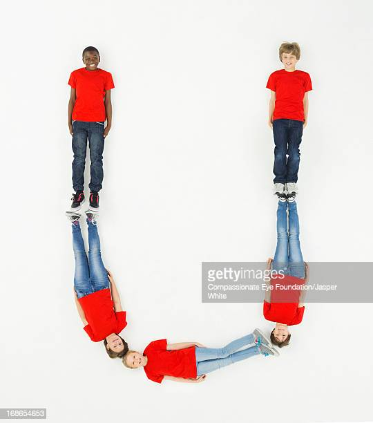 children laying in letter 'u' formation - letter u stock photos and pictures