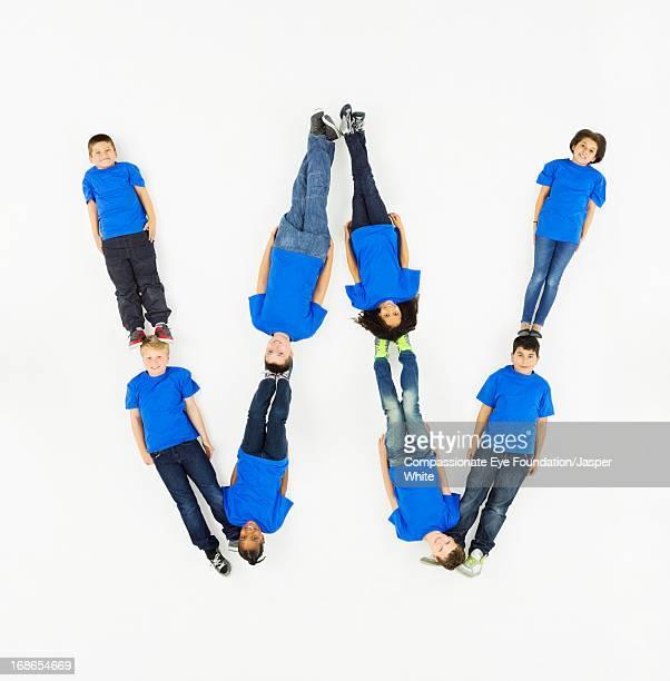 children laying in letter 'w' formation - letra w - fotografias e filmes do acervo