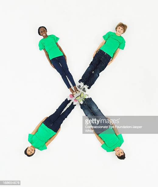 children laying in letter 'x' formation - letter x stock pictures, royalty-free photos & images