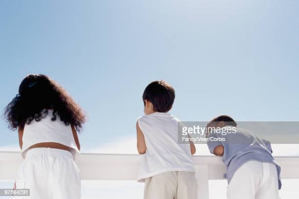 children leaning on railing - little girls bare bum stock pictures, royalty-free photos & images
