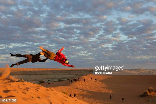 Children leap off the top of the famous Big Red Sand dune at sunrise on the final day of the The Birdsville Big Red Bash 2017 on July 6 2017 in...